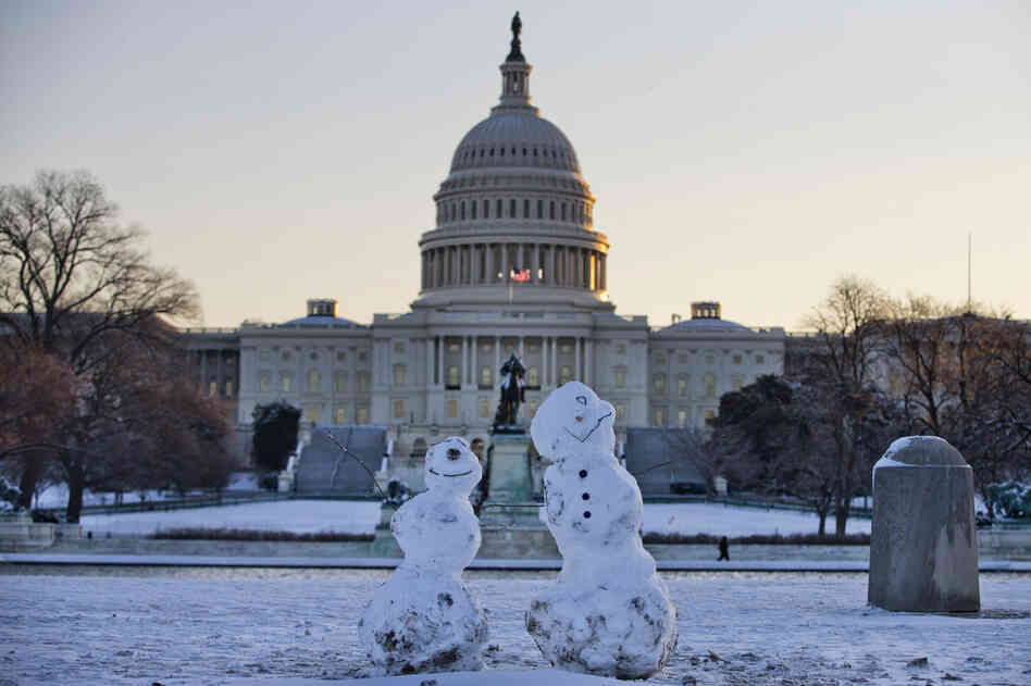 Snowmen sit in front of the Capitol in Washington, D.C. Roads are being cleared, and many school systems are closed after a storm blew through the region overnight.