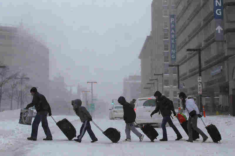 Travelers leave the Back Bay train and subway station in Boston. Dangerously cold temperatures are predicted for the rest of the day.