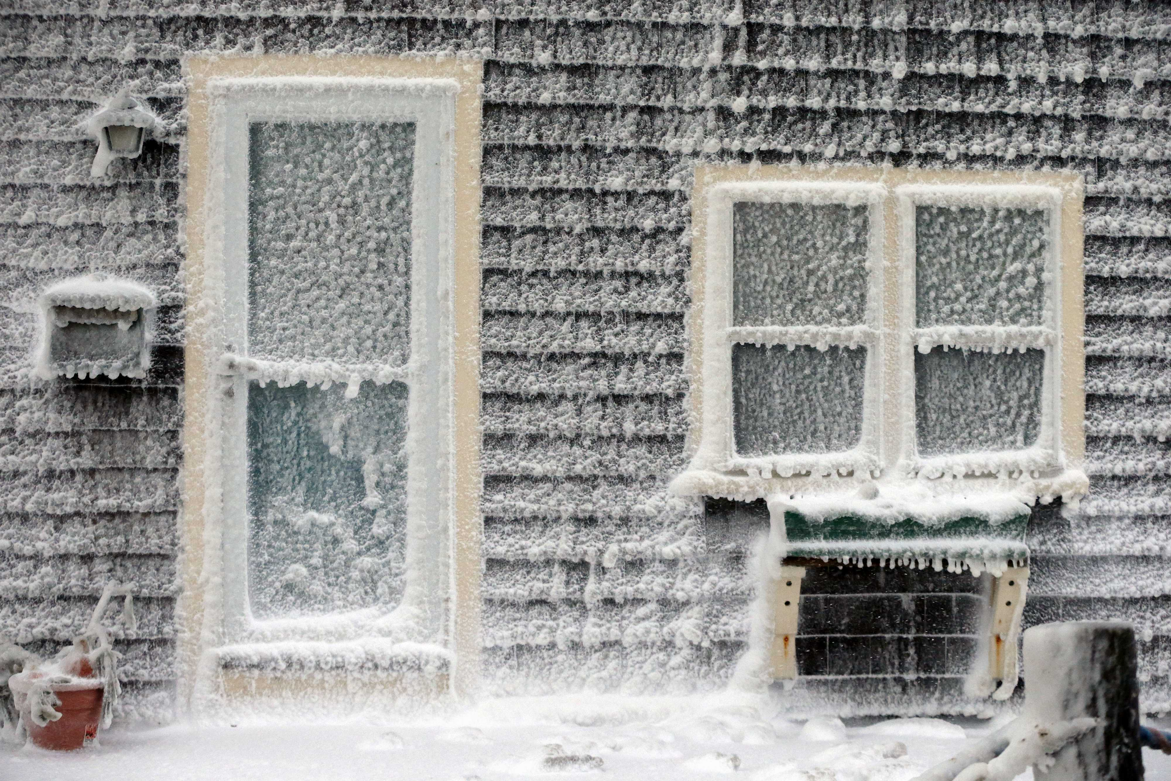 Ice from breaking waves coats a house along the shore in Scituate, Mass.