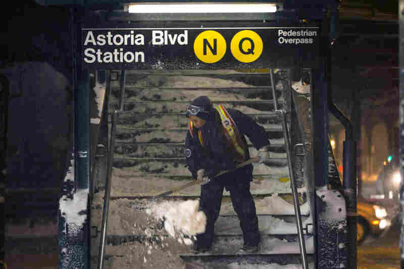 A worker clears snow from a stairway at the Astoria Boulevard subway station in Queens, N.Y. New York City public schools were closed Friday after up to 7 inches of snow fell.