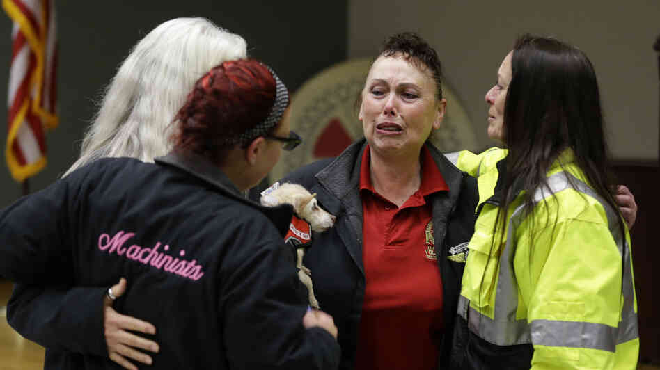 Boeing workers cry after learning that the Boeing machinists union voted to accept the company's latest contract offer to keep the assembly of the Boeing 777X airplane in Washington state.