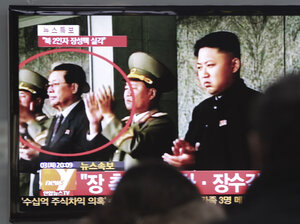 People watch a TV news program showing North Korean leader Kim Jong Un, right, and Kim's uncle, Jang Song Thaek, circled in red, at the Seoul