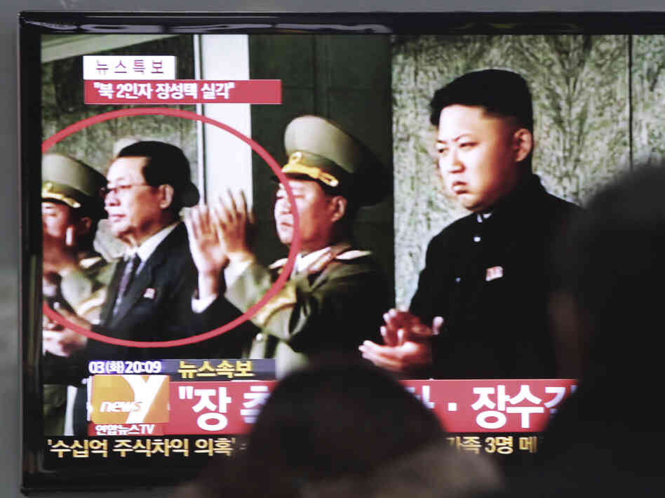 People watch a TV news program showing North Korean leader Kim Jong Un, right, and Kim's uncle, Jang Song Thaek, circled in red, at t