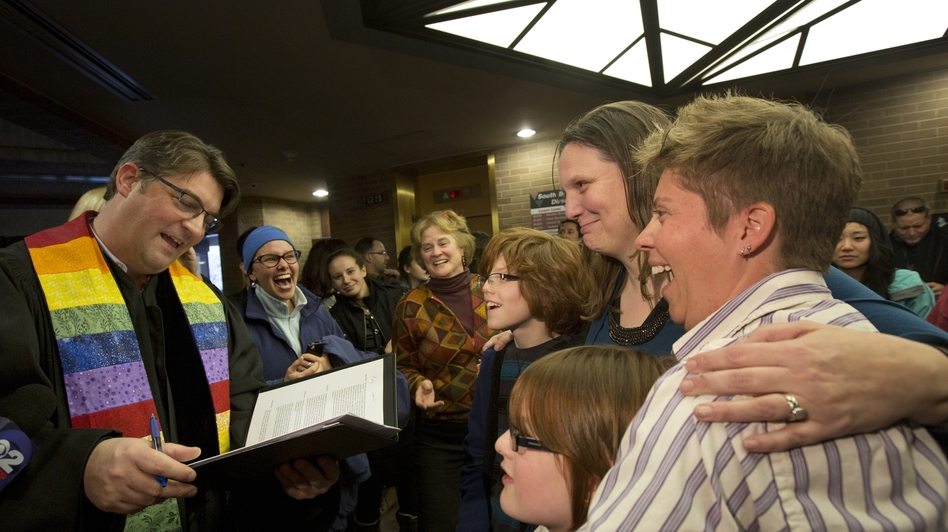 Ruth Hackford-Peer, right, and Kim Hackford-Peer are married by Rev. Curtis Price, while hugging their two children in the lobby of the Salt Lake County Clerk's Office on Dec. 20.