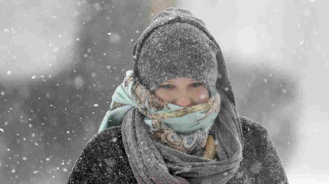 Jenny Hackett walks across a street in St. Louis, Mo., on Sunday. Subzero temperatu