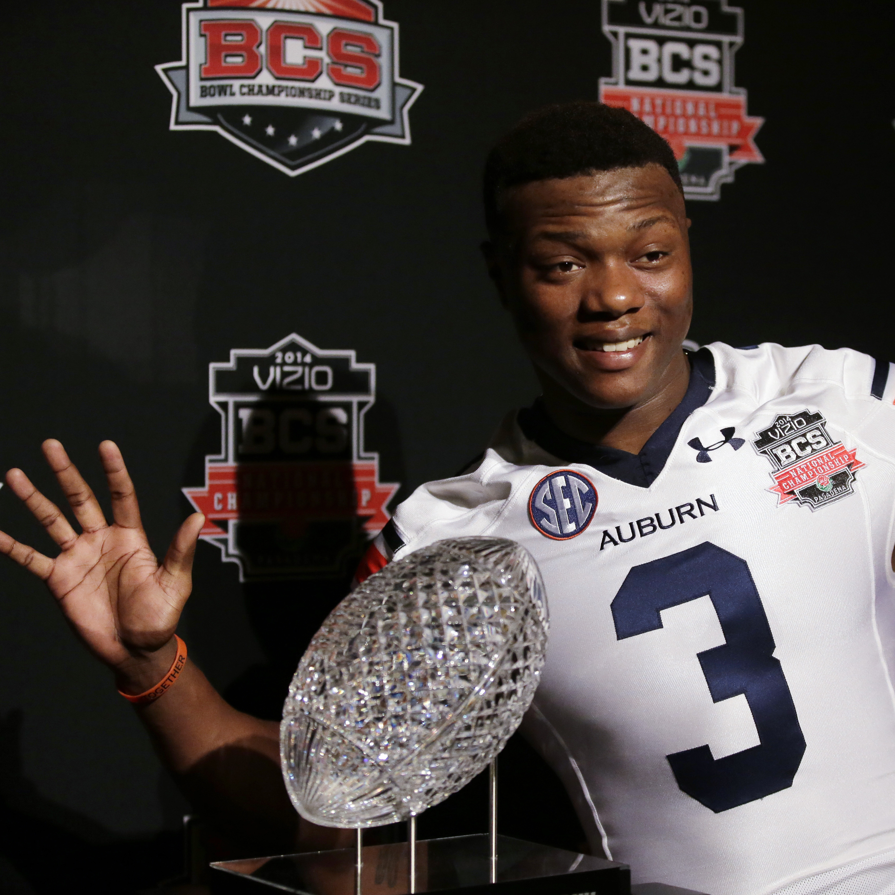 Look, But Don't Touch, Part II: Some players are superstitious and don't want to touch a trophy until they win it. Auburn wide receiver Dominic Walker poses with the NCAA's Coaches' Trophy, which goes to the winner of Monday night's game.