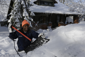John Douglas shovels snow off his car in Indianapolis, as temperatures hovered around 10 below zero. More than 12 inches of snow fell on Sunday.