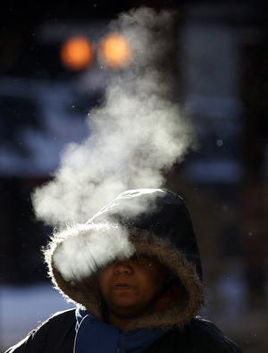 A woman walks in frigid temperatures though downtown Chicago. A blast of Arctic air gripped the midsection of the U.S. on Monday, bringing the coldest temperatures in two decades.