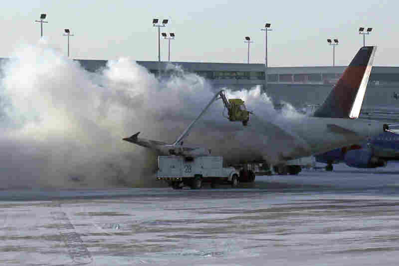 A Delta plane is deiced at Chicago Midway International Airport. More than 1,000 flights were canceled Sunday at airports throughout the Midwest; more than 400 flights were cancelled Monday.