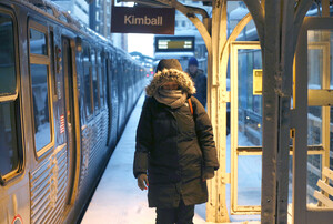 A commuter walks past warming lamps to an exit on Chicago's El tracks.