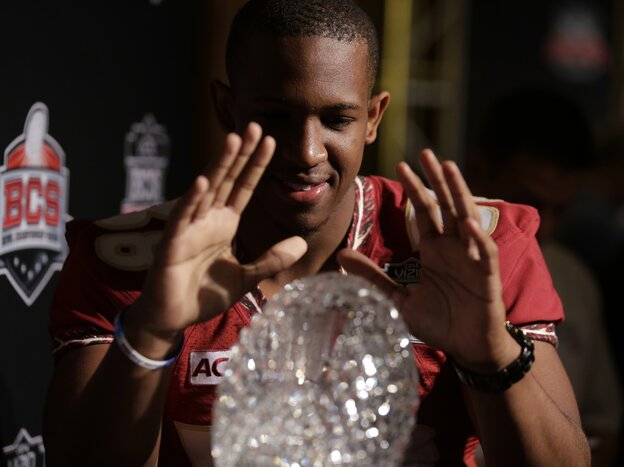 Look, But Don't Touch, Part I: Some players are superstitious and don't want to touch a trophy until they win it. Florida State defensive back Jonathan Akanbi poses with the NCAA's Coaches' Trophy, which goes to the winner of Monday night's game.