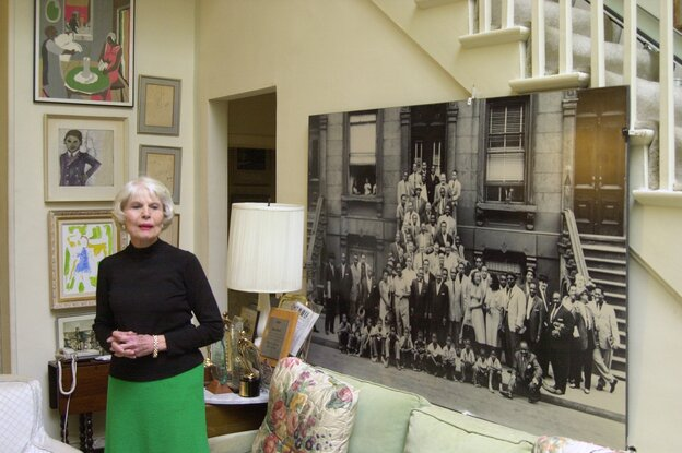 """The late documentary filmmaker Jean Bach stands next to an enlarged 1958 photograph of many jazz musicians titled """"A Great Day in Harlem."""" Her documentary about the photo shoot was nominated for an Academy Award in 1995."""