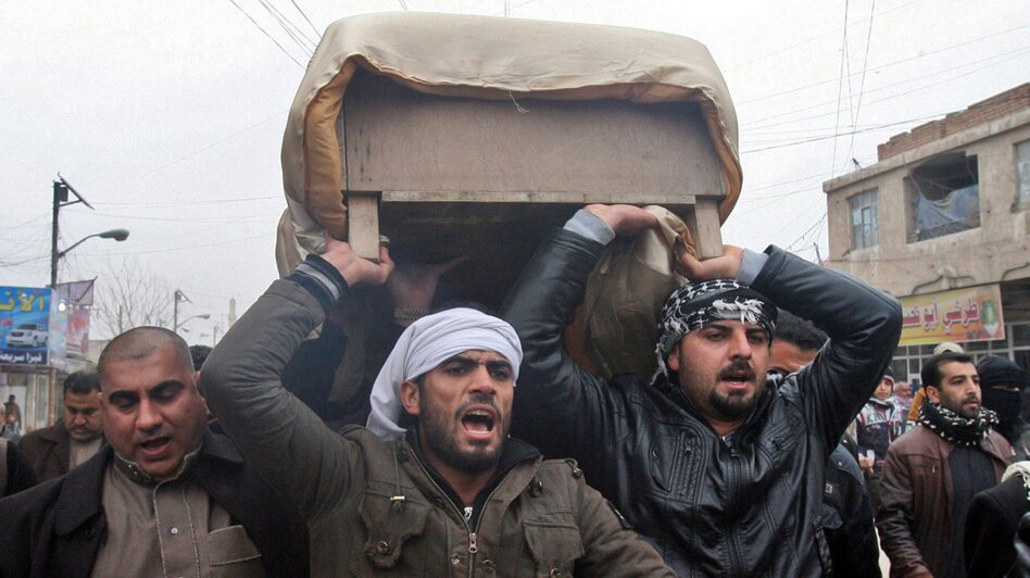 Iraqi Sunni men carry the coffin of a person killed by Iraqi army fire in Fallujah, in western Iraq, on Saturday. Sunni extremists have been battling Iraqi government forces in the region, in fighting reminiscent of violence a decade ago.