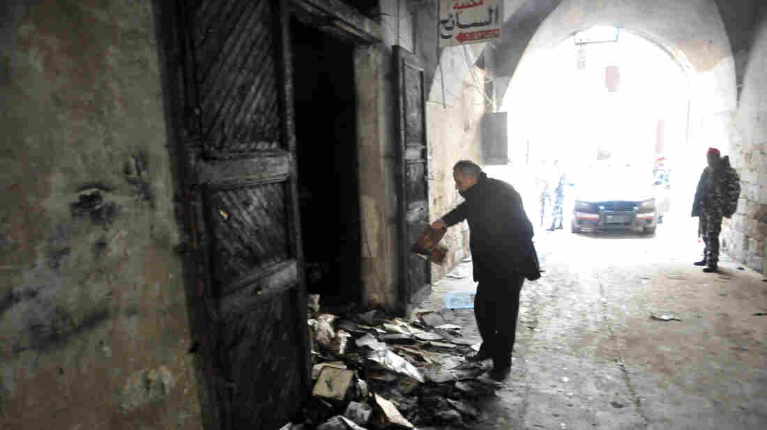 A man inspects burnt books in north Lebanon's majority Sunni city of Tripoli on Saturday, a day after a decades-old library owned by a Greek Orthodox priest was burned.