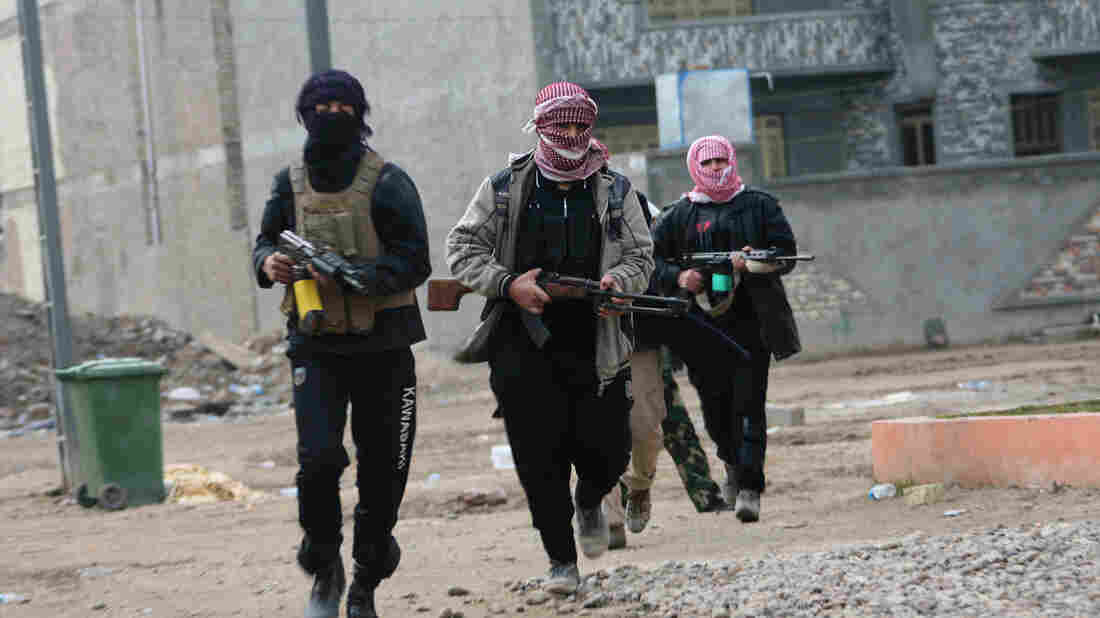Gunmen patrol during clashes with Iraqi security forces in Fallujah, on Jan. 5, 2014. Al-Qaida has been battling to take back both Ramadi and Fallujah in Anbar province in Iraq.