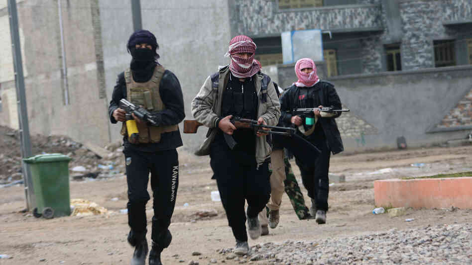Gunmen patrol during clashes with Iraqi security forces in Fallujah, on Jan. 5, 2014. Al-Qaida has been battling to take back both Ramadi and Fallujah in Anbar province in