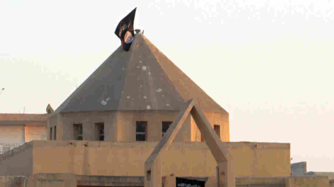The flag of the Islamic State of Iraq and Syria, or ISIS, flutters