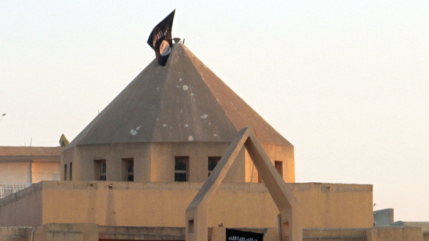 The flag of the Islamic State of Iraq and Syria, or ISIS, flutters on the dome of an Armenian Catholic Church in the northern rebel-held Syrian city of Raqqa on Sept. 28, 2013. At first, Syrian rebels and civilians welcomed the experienced Islamist fighters, and the groups fought together to take over the city from Syrian troops. Now, many Syrians fear and resent ISIS. (AFP/Getty Images)