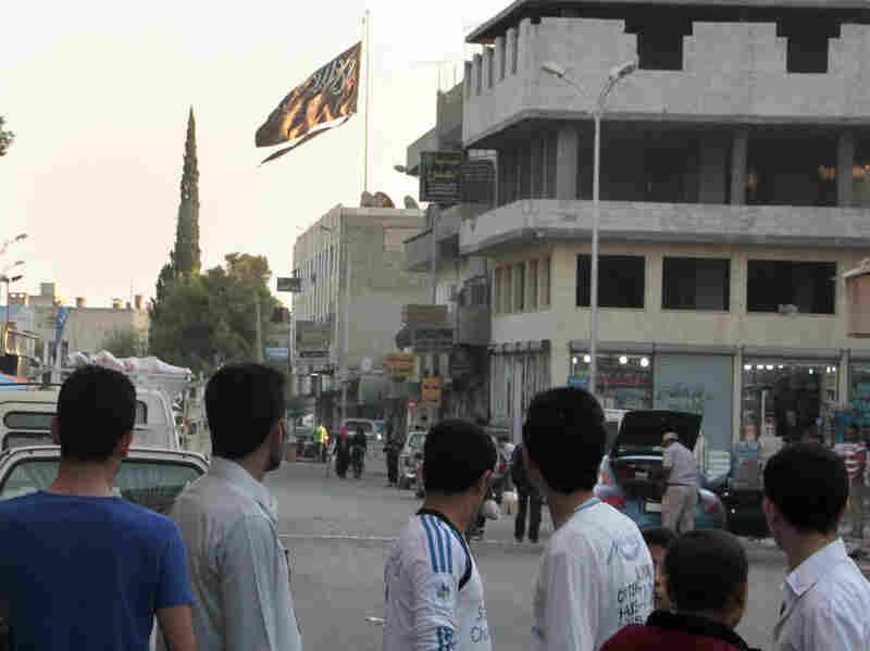 Men look at a jihadist flag flying over Raqqa on Sept. 28, 2013.
