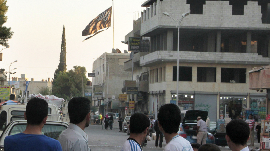 Men look at a jihadist flag flying over Raqqa on Sept. 28, 2013. (AFP/Getty Images)
