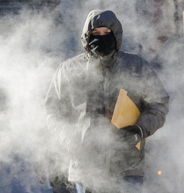 A man walks through a steam cloud in frigid cold temperatures Tuesday in Manhattan.