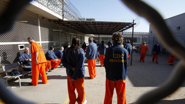 Inmates walk around a recreation yard at the Deuel Vocational Institution in Tracy, Calif., in January 2012.