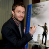 Chris Hardwick, the host of Talking Dead, autographs a poster for the show his show discusses: The Walking Dead.