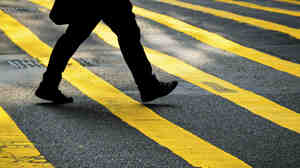 The lower-half of a person walking across a yellow-striped crosswalk in the city.