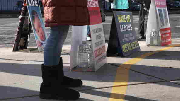 Anti-abortion protesters assemble outside the Planned Parenthood clinic in Boston on Dec. 7. The protesters are legally behind the 35-foot buffer zone, which is marked by a painted yellow line on the sidewalk.