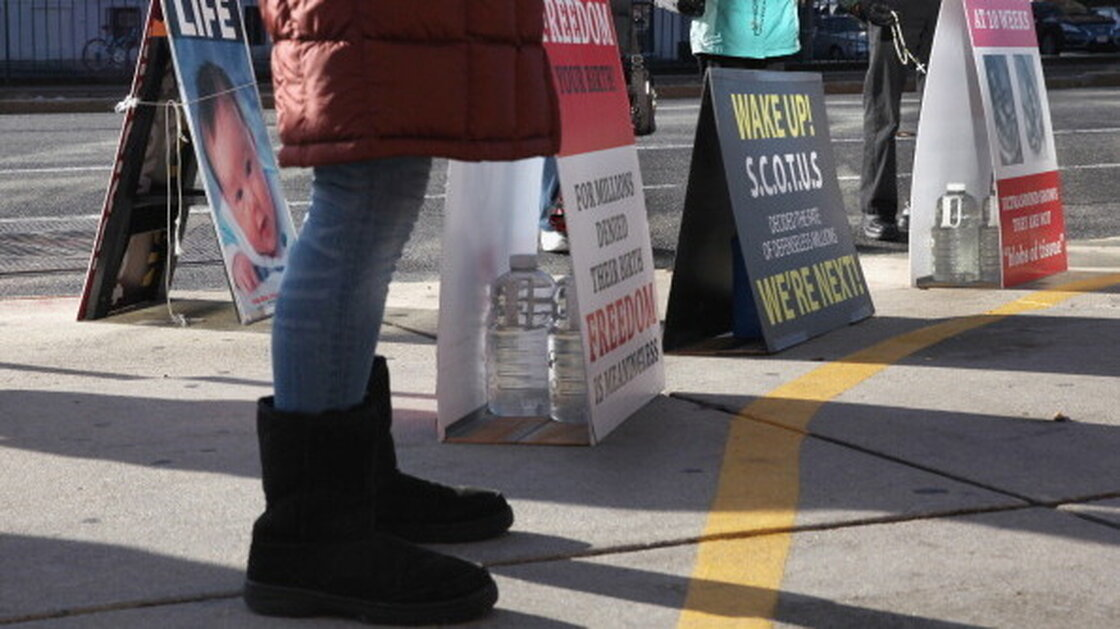 Anti-abortion protesters assemble outside the Planned Parenthood clinic in Boston on Dec. 7, 2013. The protesters are legally behind the 35-foot buffer zone, which is marked by a painted yellow line on the sidewalk.