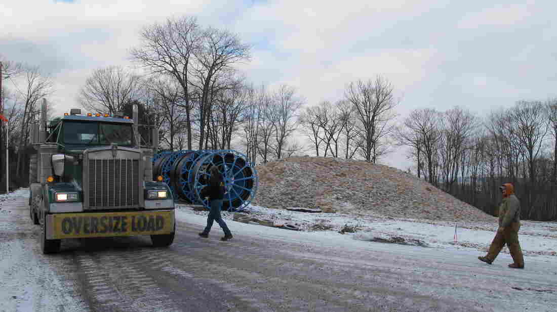An oversized truck load slowly moves equipment along an icy mountain road in Pennsylvania's Tiadaghton State Forest.