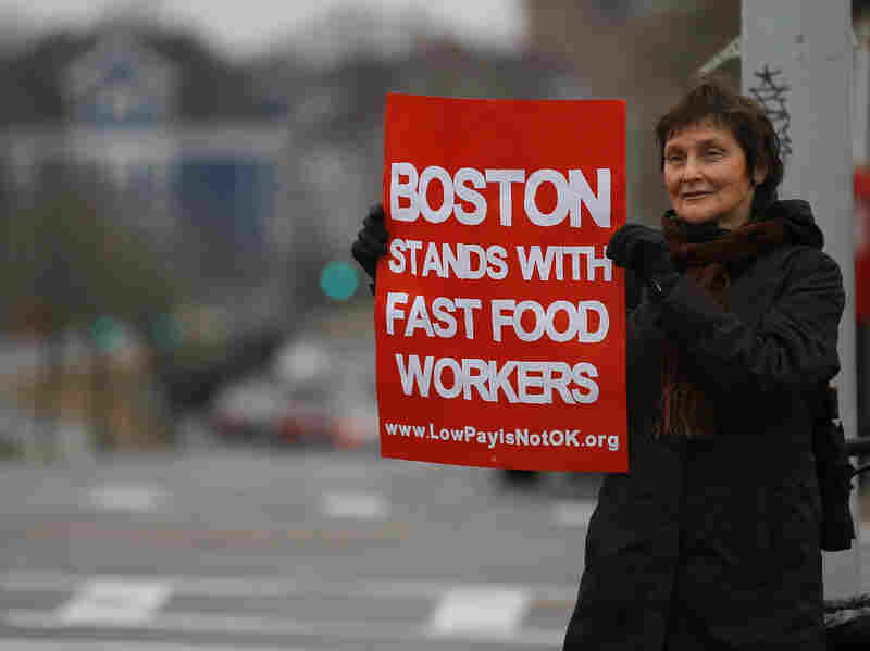 Trish Gallagher holds a sign for passing motorists to read during a demonstration in support of a higher minimum wage near a Burger King in Boston on Dec. 5. Massachusetts is one of several states considering a minimum wage ballot measure.