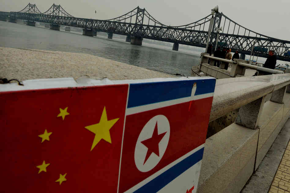 The Chinese and North Korean flags are seen attached to a railing as trucks carrying Chinese-made goods cross into North Korea on the Sino-Korean Friendship Bridge at the Chinese border town of Dandong on Dec. 18, 20