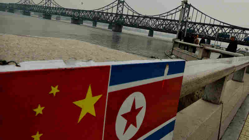 The Chinese and North Korean flags are seen attached to a railing as trucks carrying Chinese-made goods cross into North Korea on the Sino-Korean Friendship Bridge at the Chinese border town of Dandong on Dec. 18, 2013. Ties between the two longtime allies are strained after the execution of the North Korean official in charge of economic relations with China.