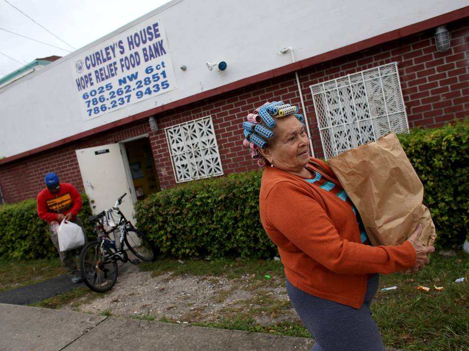 Elba Salsado walks with her groceries after receiving them from a food bank in Miami.