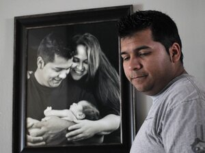 Erick Munoz stands by a photo of his wife, Marlise  Munoz, at home in Fort Worth, Texas, on Jan. 3. She is being kept on life support in a local hospital against the family's wishes.