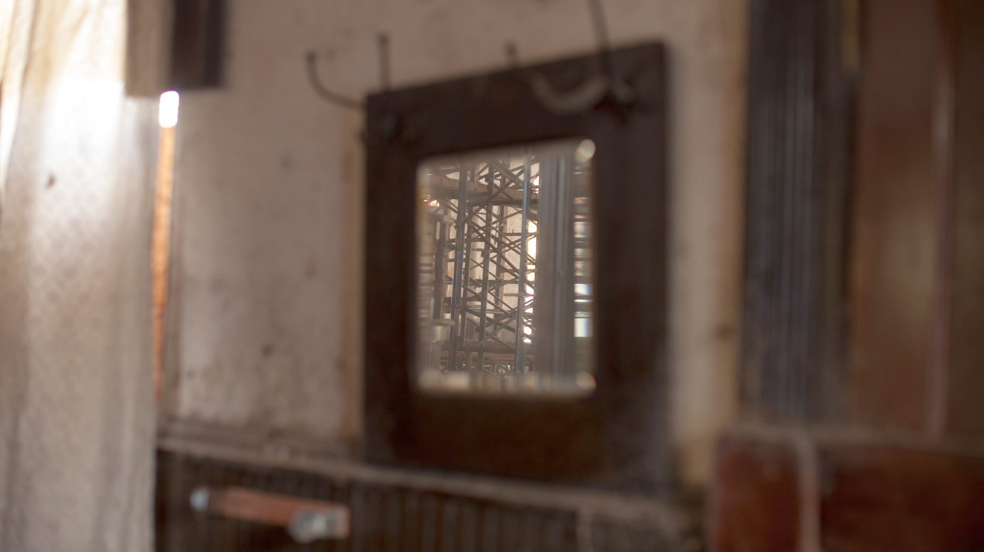 A mirror reflects the scaffolding that holds up the interior of the church.