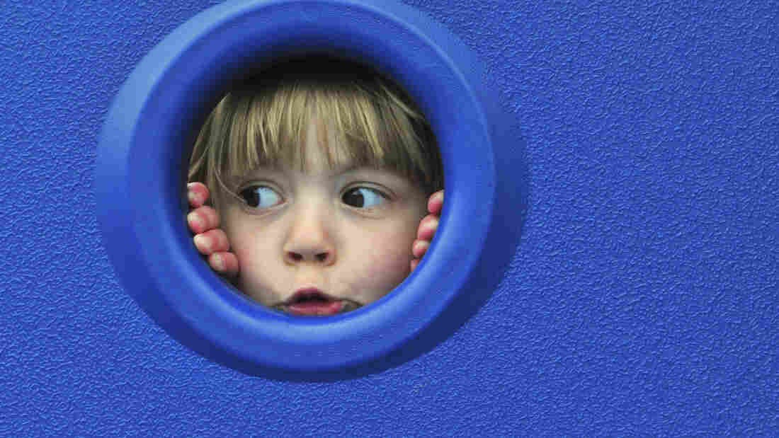 A child looks through a round opening in a blue wall.