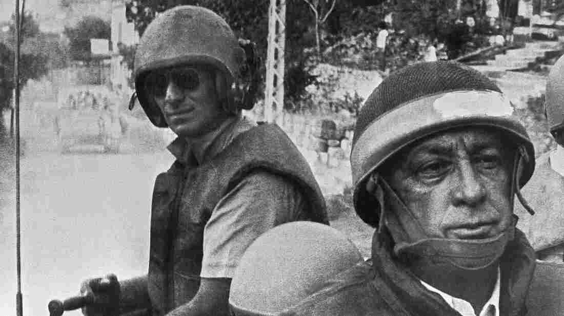 "Israeli Defense Minister Ariel Sharon (right), in combat helmet and flak jacket, rides with his troops on June 15, 1982, as they head deeper into Lebanon. The Israelis drove Arafat and his Palestine Liberation Organization out of Lebanon, but Sharon was later found ""indirectly responsible"" for the killings of hundreds of Palestinian civilians carried out by a Lebanese militia allied with Israel."