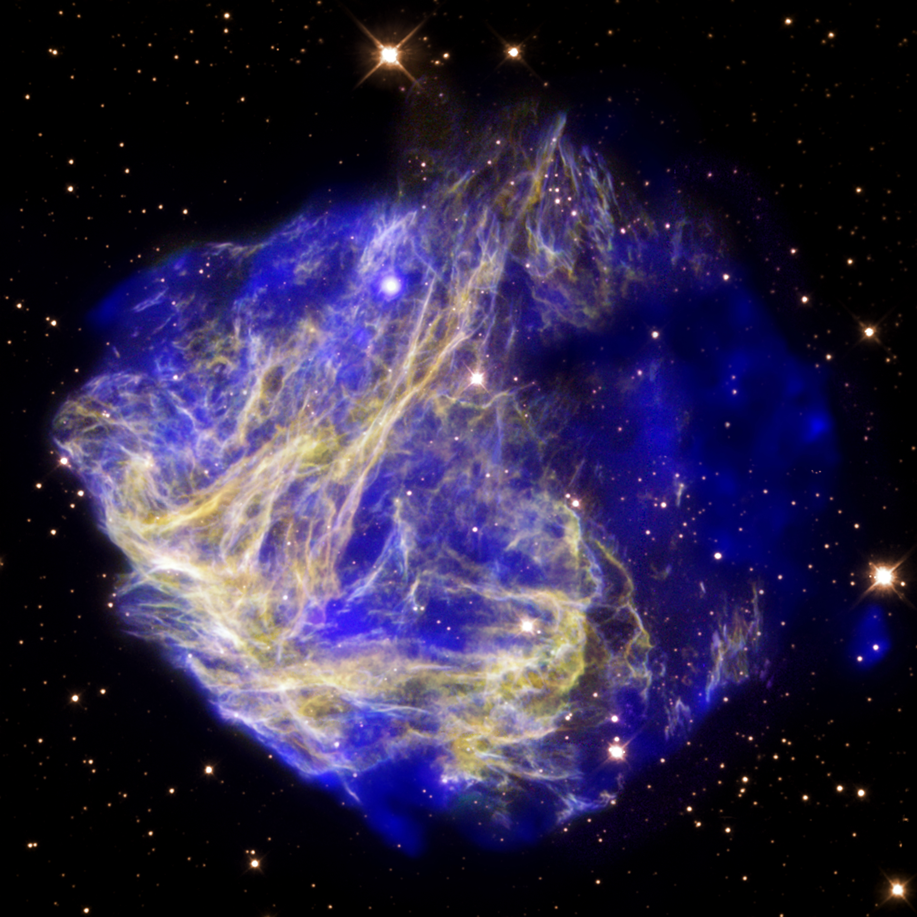 'This composite image of data from Chandra (blue) and Hubble (yellow and purple) depicts the scene of a supernova explosion's aftermath.  The X-ray data reveal a bullet-like structure to the lower right that appears to have been blown out of the remnant.   The detection of the bullet, which is traveling at some 5 million miles per hour, is evidence that the explosion that created the remnant wa...