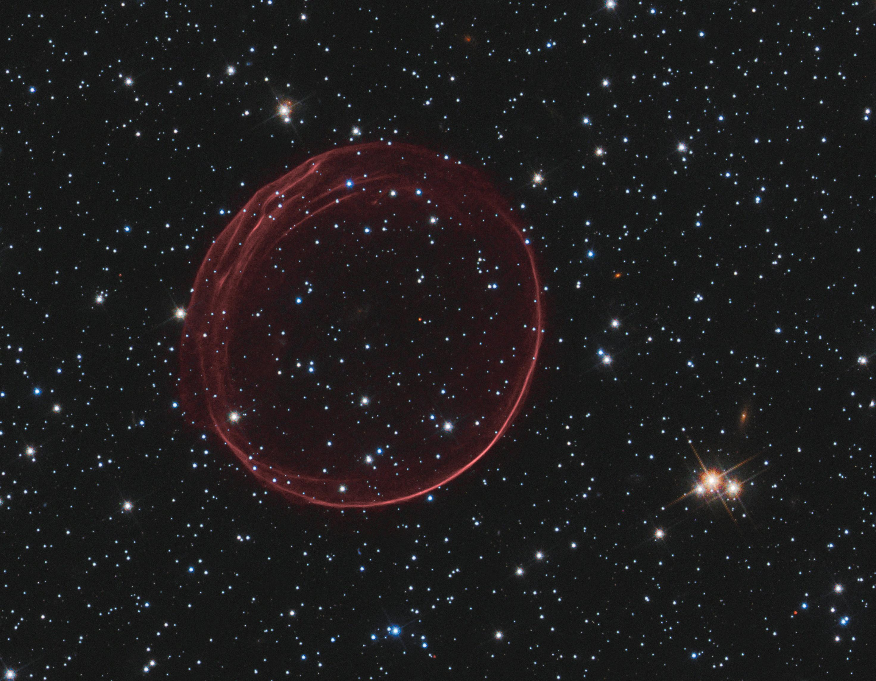 A delicate sphere of gas, photographed by NASA's Hubble Space Telescope, floats serenely in the depths of space. The pristine shell, or bubble, is the result of gas that is being shocked by the expanding blast wave from a supernova. Called SNR 0509-67.5 (or SNR 0509 for short), the bubble is the visible remnant of a powerful stellar explosion in the Large Magellanic Cloud (LMC), a small galaxy ...