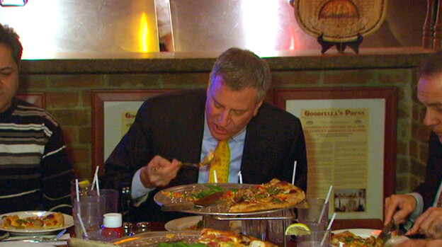 In this image taken from video and provided by New York City Hall, New York Mayor Bill de Blasio eats pizza with a fork at Goodfellas Pizza in the Staten Island on Friday.