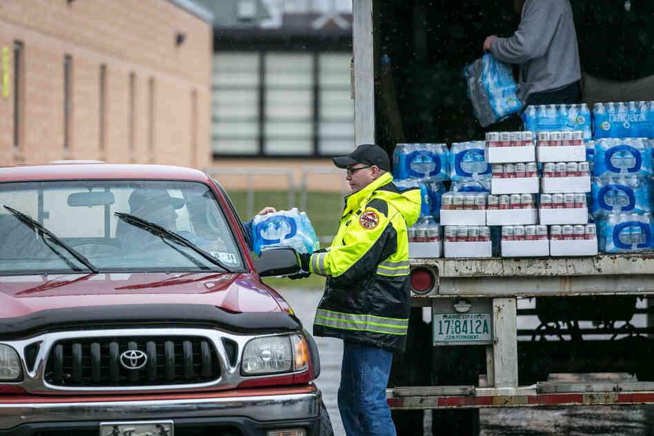 Members of the Nitro Volunteer Fire Department distribute water to local residents on Saturday.