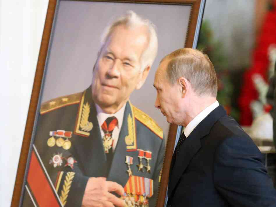 Russian President Vladimir Putin pauses by a portrait of Mikhail Kalashnikov at the arms designer's funeral in December.