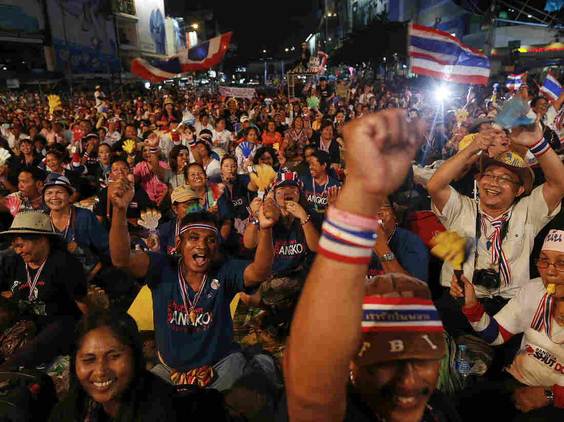 Anti-government protesters cheer as they occupy a major intersection in central Bangkok on Monday. Tens of thousands of anti-government protesters occupied parts of the capital.