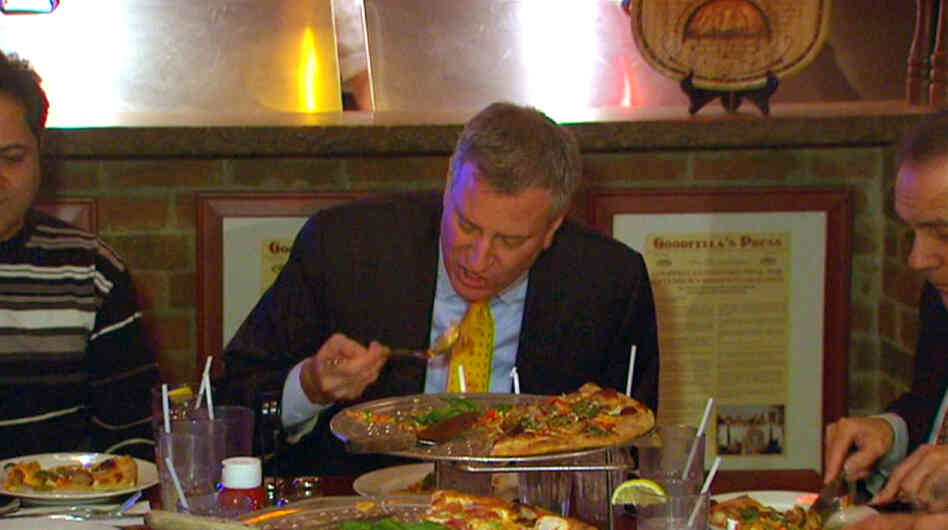 In this image taken from video and provided by New York City Hall, New York Mayor Bill de Blasio eats pizza with a fork at Goodfellas Pizza on Staten Island on Friday.