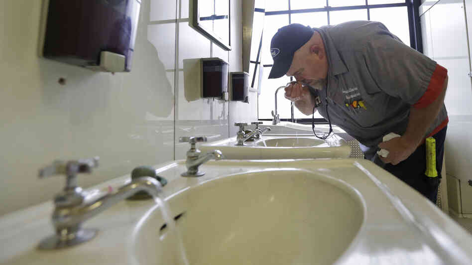 In West Virginia, a ban on water use has been lifted in at least three areas affected by a chemical spill. Here, Al Jones of the state's General Services department tests the water as he flushes a faucet and opens a restroom on the first floor of the Capitol in Charleston on Monday.