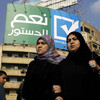 """Egyptians walk under a billboard with Arabic that reads, """"yes to the constitution, Egyptians love their country,"""" in Cairo's Tahrir Square on Jan. 11. Many Egyptians say there is no real choice in the country's referendum on a new constitution."""