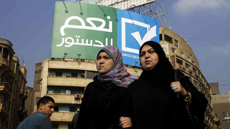 "Egyptians walk under a billboard with Arabic that reads, ""yes to the constitution, Egyptians love their country,"" in Cairo's Tahrir Square on Jan. 11. Many Egyptians say there is no real choice in the country's referendum on a new constitution."