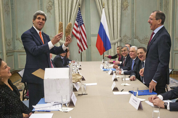 U.S. Secretary of State John Kerry holds up a pair of Idaho potatoes as a gift for Russia's Foreign Minister Sergei Lavrov, standing right, at the start of their meeting at the U.S. Ambassador's residence in Paris on Monday.